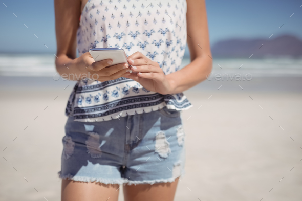 Mid section of woman using mobile phone at beach - Stock Photo - Images
