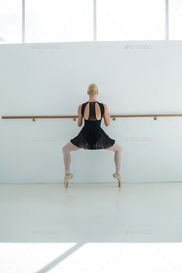 Ballerina stretching at barre - Stock Photo - Images