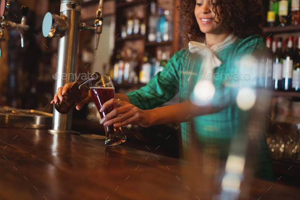 Waitress pouring beer in pilsner glass at counter - Stock Photo - Images