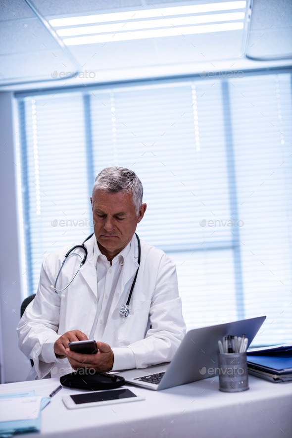 Doctor sitting at tablet and using mobile phone - Stock Photo - Images