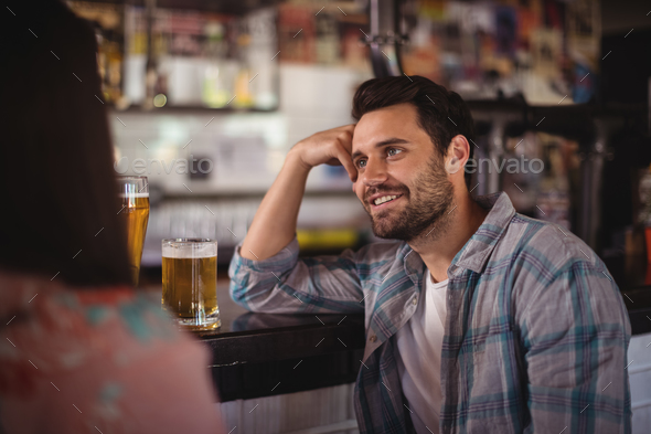 Happy couple interacting while having beer at counter - Stock Photo - Images