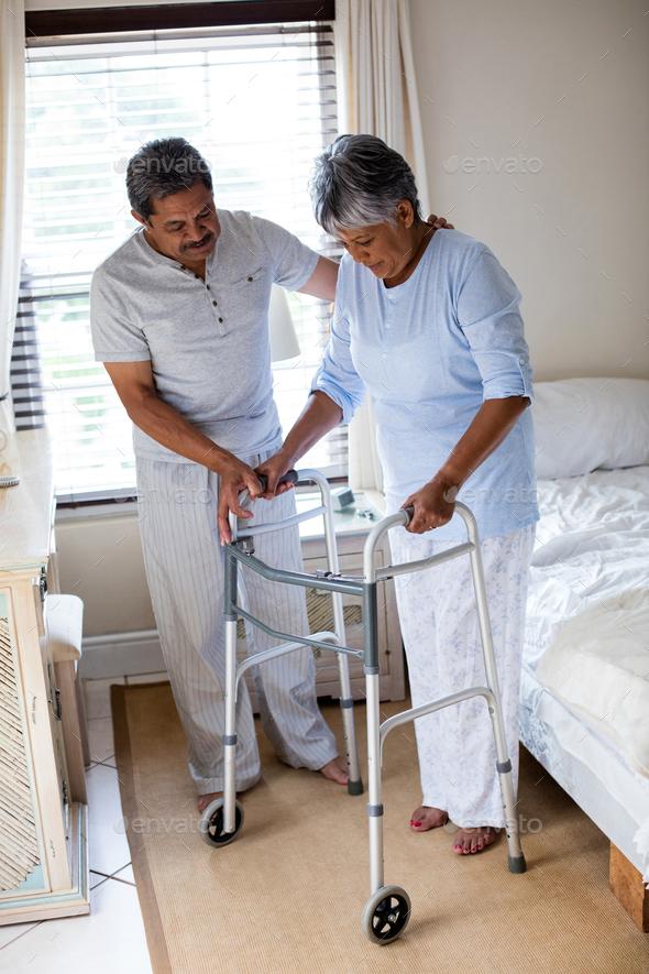 Senior man helping senior woman to walk with walker - Stock Photo - Images