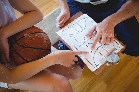 Close up of coach explaining diagram to female basketball player - Stock Photo - Images