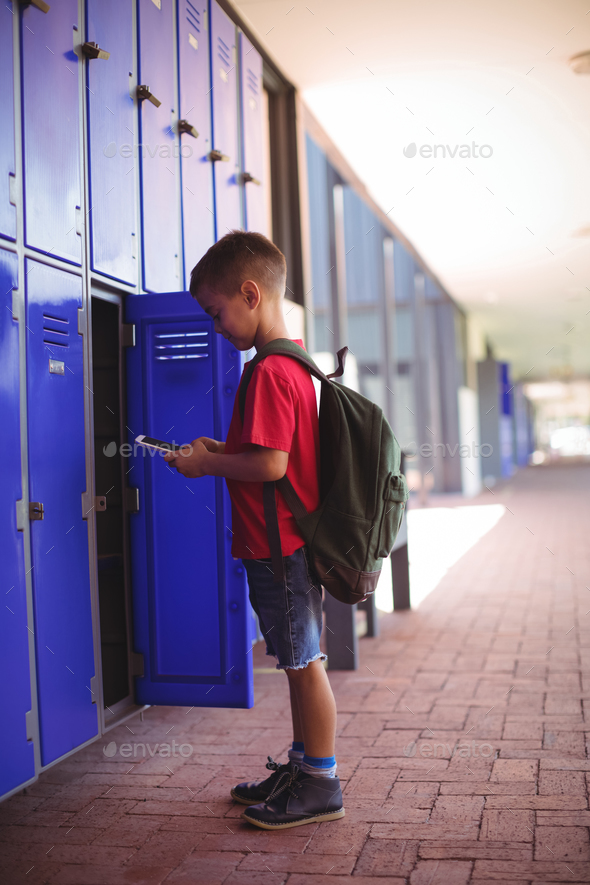 Side view of boy using mobile phone by open locker - Stock Photo - Images