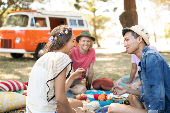 Friends looking at woman laughing while sitting on field - Stock Photo - Images
