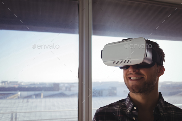 Businessman wearing virtual reality headset in office - Stock Photo - Images