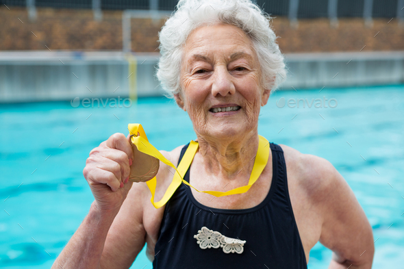 Senior woman showing gold medal at poolside - Stock Photo - Images