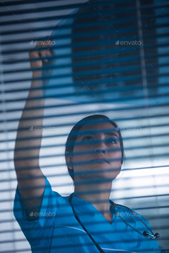 Nurse examining X-ray report - Stock Photo - Images