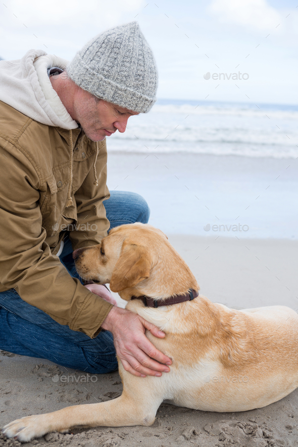 Man pampering dog while sitting - Stock Photo - Images