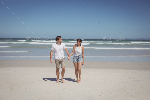 Full length of couple holding hands at beach - Stock Photo - Images