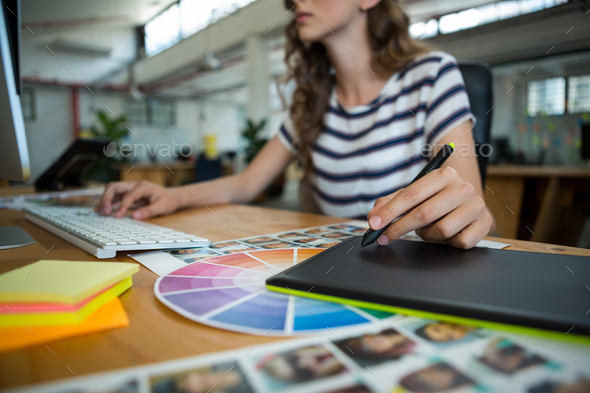 Mid section of female graphic designer using graphics tablet at desk - Stock Photo - Images
