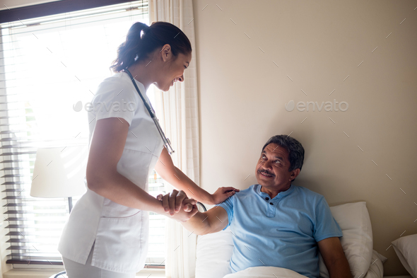 Female doctor interacting with senior patient in bedroom - Stock Photo - Images