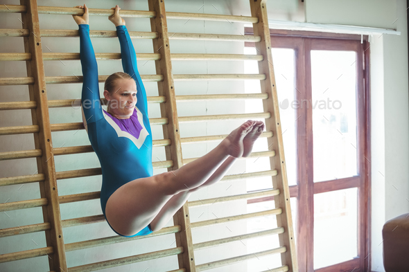 Female gymnast practicing gymnastics on wooden wall bar - Stock Photo - Images