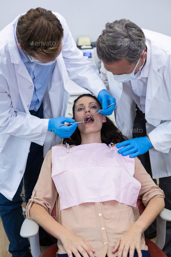 Dentists examining a female patient with tools - Stock Photo - Images
