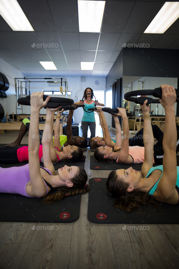 Female trainer assisting group of women with pilates ring exercise - Stock Photo - Images