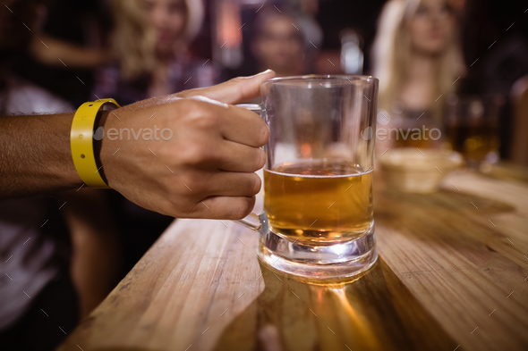 Cropped image of hand holding beer glass - Stock Photo - Images