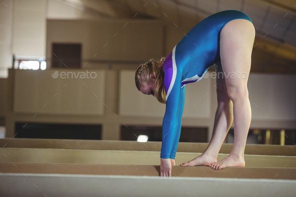 Female gymnast practicing gymnastics on the balance beam - Stock Photo - Images