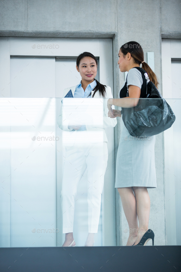 Businesswomen standing by elevator and having a conversation - Stock Photo - Images