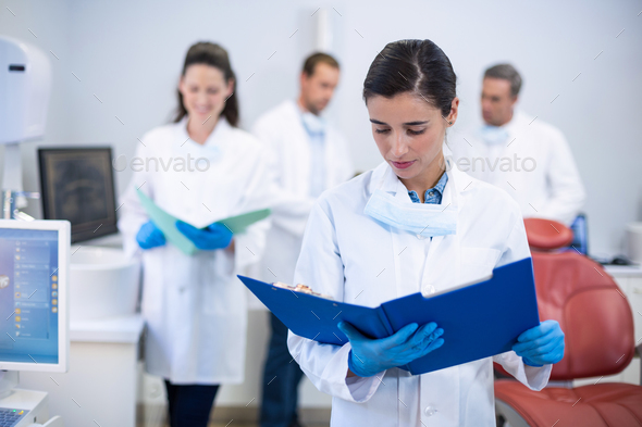 Dentist looking at reports in dental clinic - Stock Photo - Images