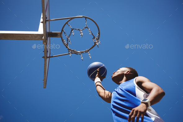 Low angle view of teenage boy playing basketball - Stock Photo - Images