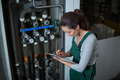 Female factory worker maintaining record on clipboard in factory - PhotoDune Item for Sale