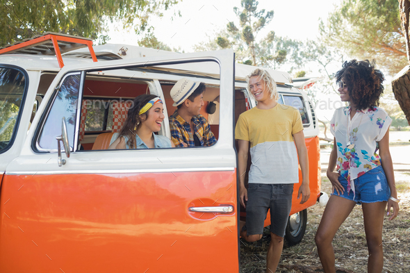 Smiling friends standing by camper van at campsite - Stock Photo - Images