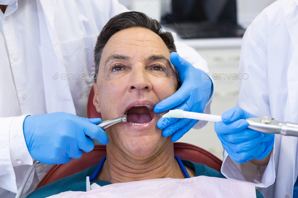 Dentist examining a male patient with tools - Stock Photo - Images