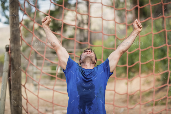 Happy man raising his hands during obstacle course - Stock Photo - Images