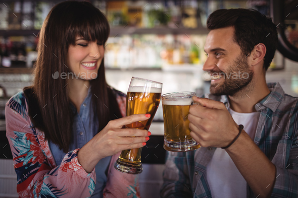 Happy couple toasting glasses of beer at counter - Stock Photo - Images