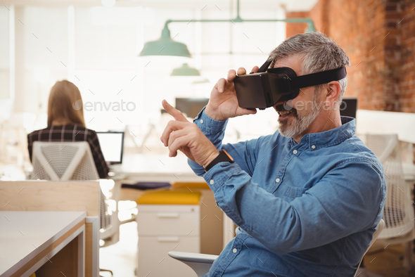 Male executive using virtual reality headset at desk - Stock Photo - Images