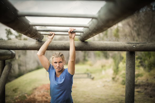 Fit woman climbing monkey bars during obstacle course - Stock Photo - Images