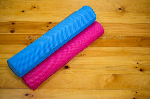 Rolled-up exercise mat on wooden floor - Stock Photo - Images
