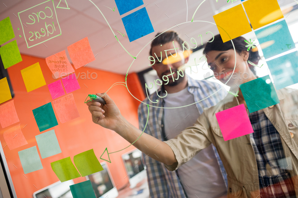 Male and female executives discussing over sticky notes - Stock Photo - Images
