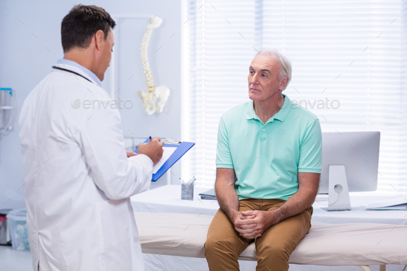 Doctor writing on clipboard in clinic - Stock Photo - Images