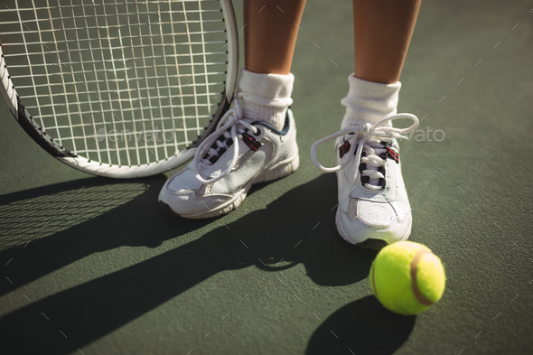 Low section of girl with racket and tennis bal - Stock Photo - Images