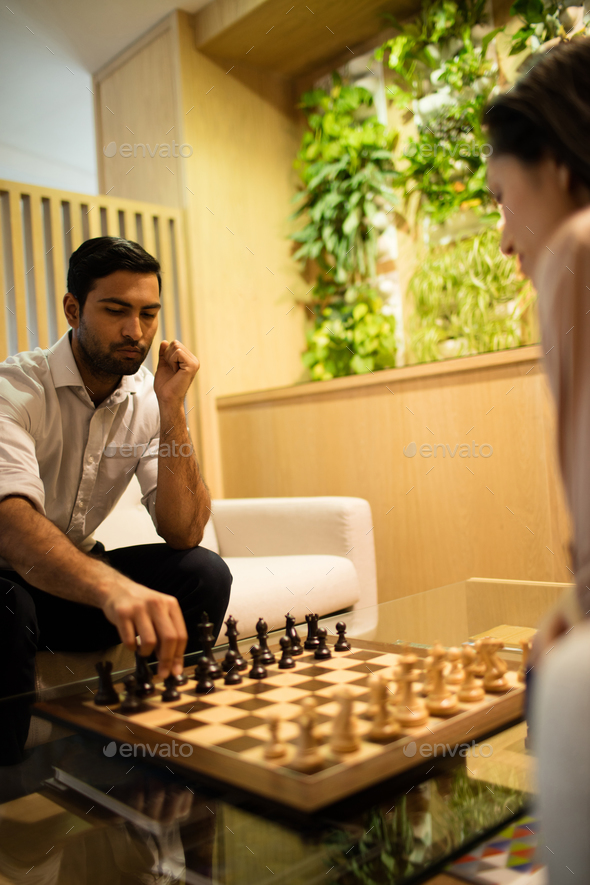 Businessman playing chess with female colleague - Stock Photo - Images