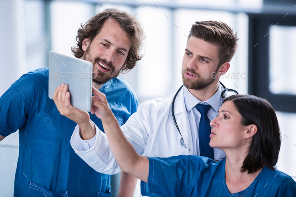 Surgeons and doctor looking at digital tablet - Stock Photo - Images