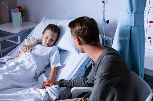 Father sitting beside her daughter lying on a hospital bed - Stock Photo - Images