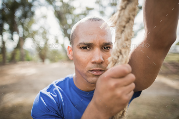 Portrait of fit man climbing rope during obstacle course - Stock Photo - Images