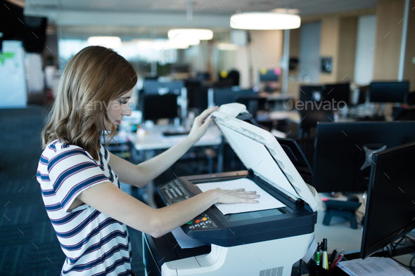 Businesswoman using copy machine in office - Stock Photo - Images