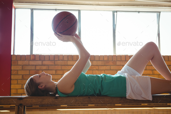 Woman playing with basketball while lying on bench in court - Stock Photo - Images