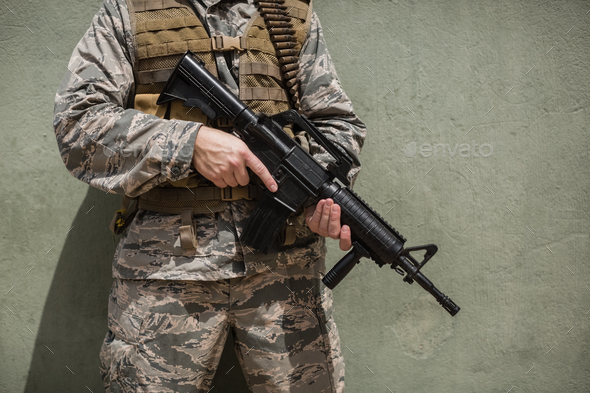 Mid section of military soldier standing with a rifle against concrete wall - Stock Photo - Images