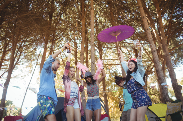 Low angle view of friends dancing against trees at campsite - Stock Photo - Images