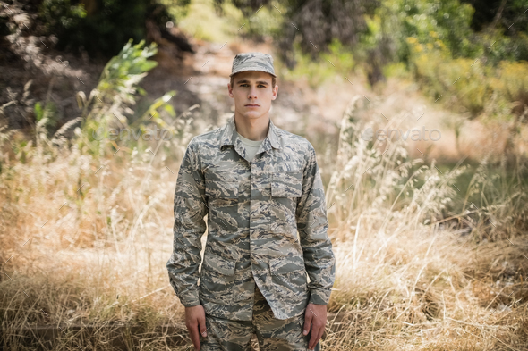 Portrait of military soldier standing in grass - Stock Photo - Images