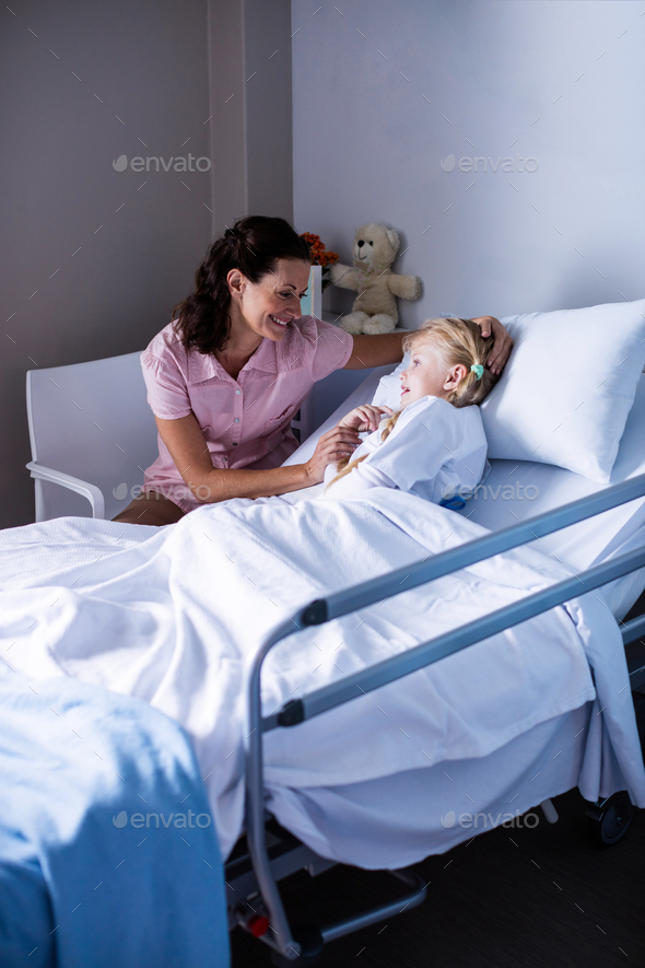 Female doctor consoling patient during visit in ward - Stock Photo - Images