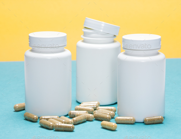 Scattered capsules with white plastic jars - Stock Photo - Images
