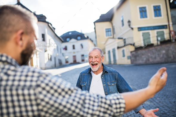 An adult hipster son and his overjoyed senior father in town, greeting. - Stock Photo - Images