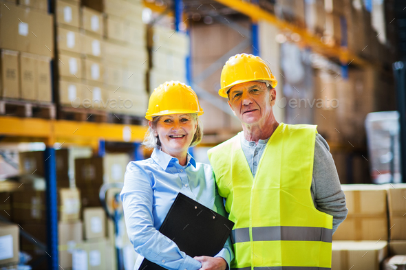 Senior woman manager and man worker standing in a warehouse. - Stock Photo - Images