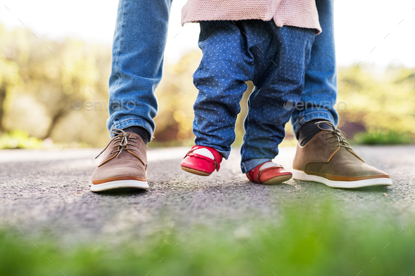 First steps of a toddler girl outside in spring nature. - Stock Photo - Images