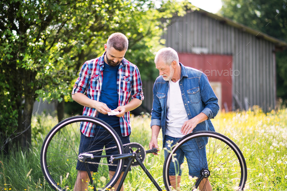 An adult hipster son and senior father repairing bicycle puncture n a sunny day. - Stock Photo - Images